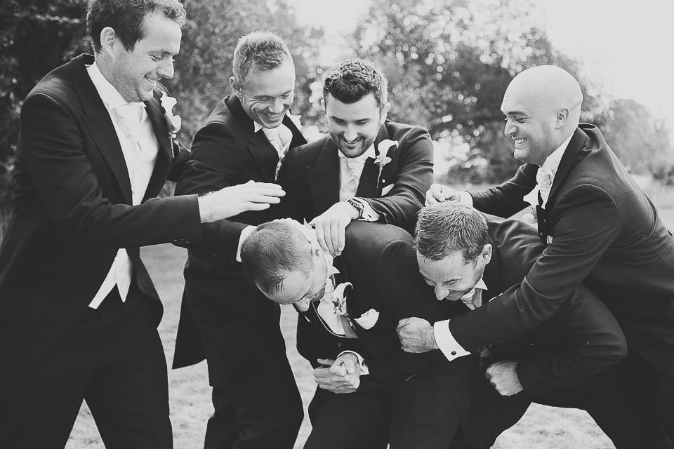 Groomsmen play fighting with the groom on the lawn at Sopley Mill