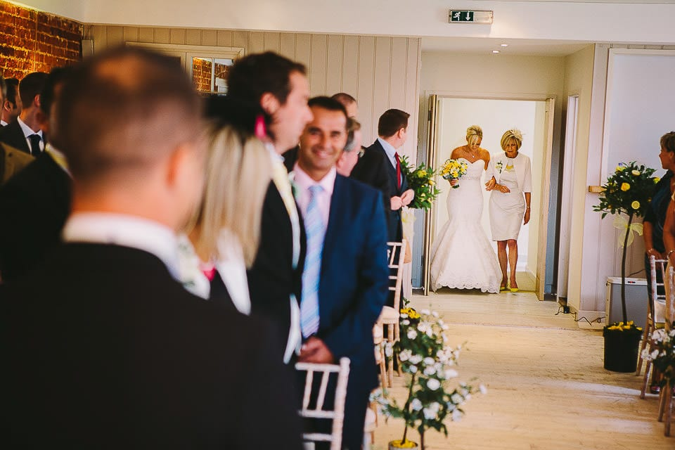 View down the aisle of bride and her mother entering the room at Sopley Mill