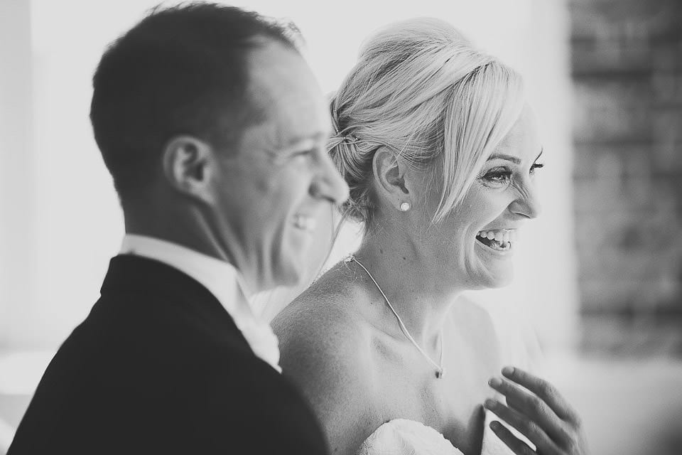 Black and white image of bride and groom laughing at Sopley Mill