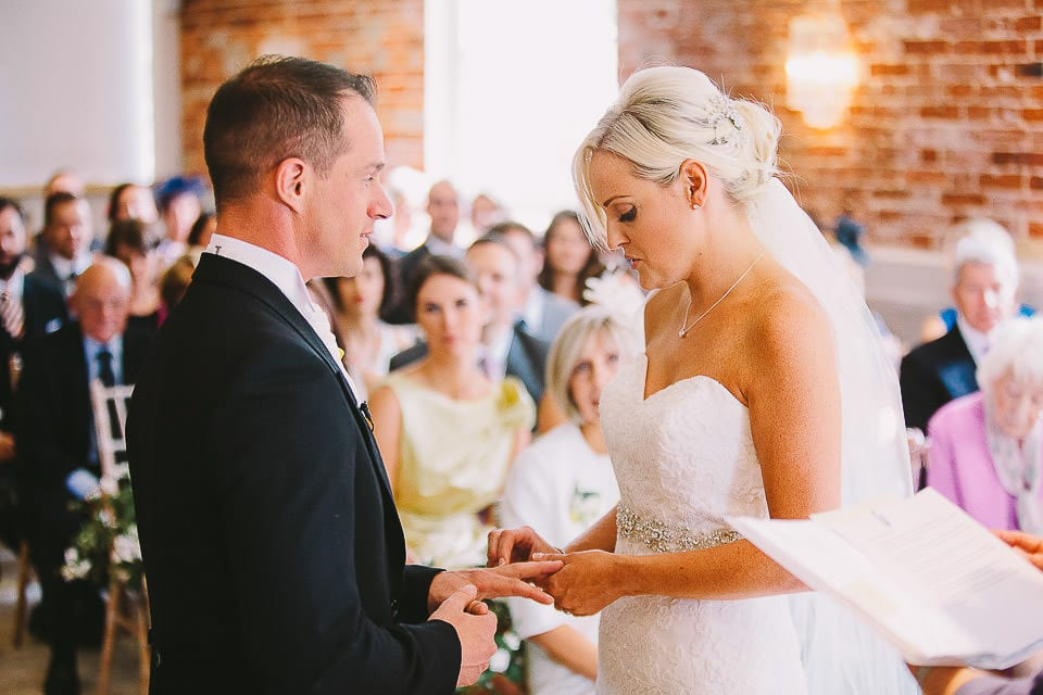 Bride and groom exchanging rings at Sopley Mill