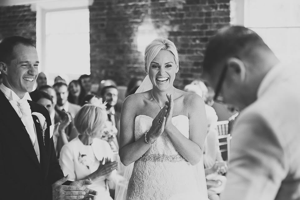 Bride and groom laughing at guests reading during the wedding ceremony at Sopley Mill