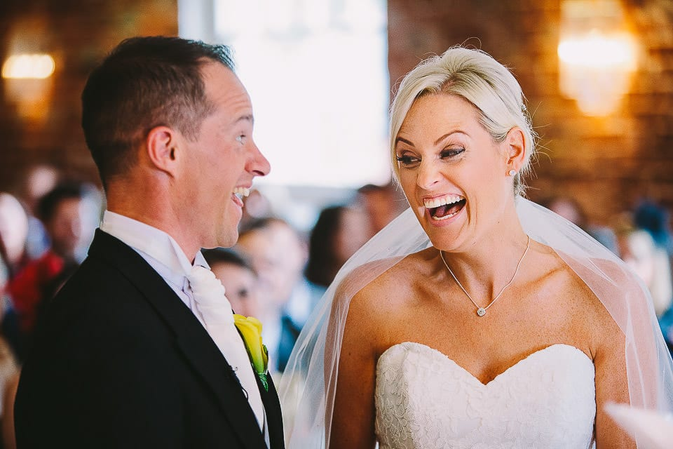 Bride and groom laughing during ceremony at Sopley Mill