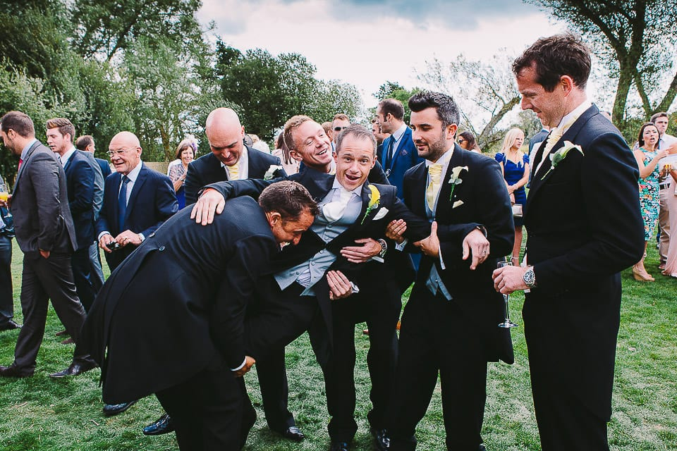 Groomsmen picking up the groom outside at Sopley Mill