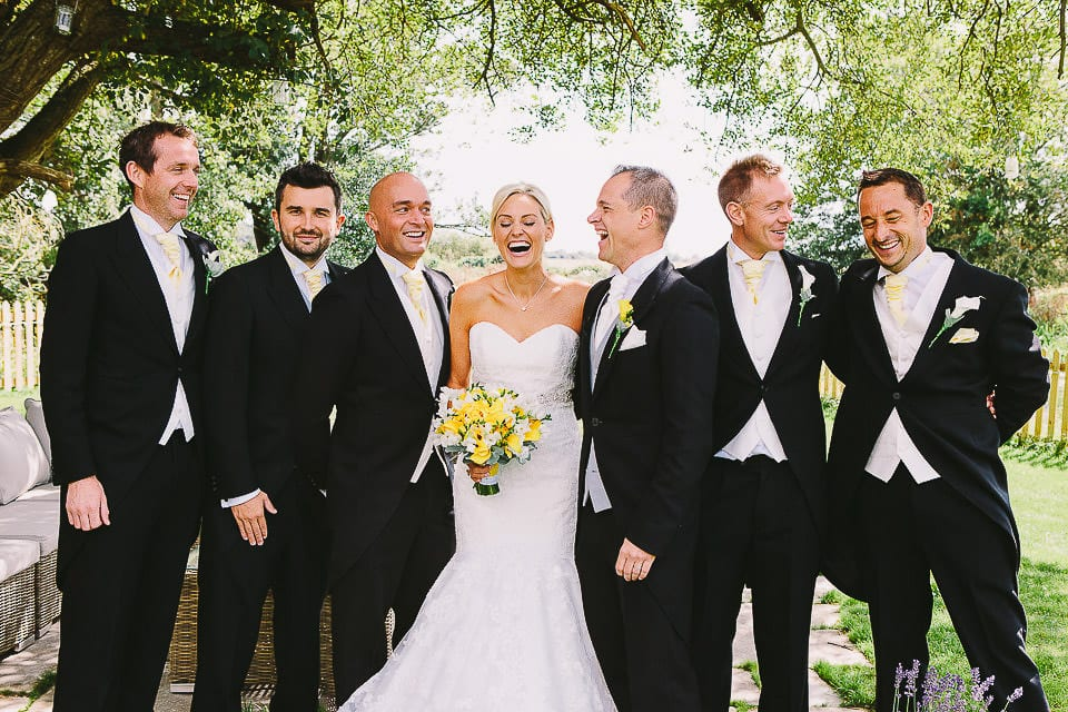 Bride and groom with groomsmen under the trees at Sopley Mill