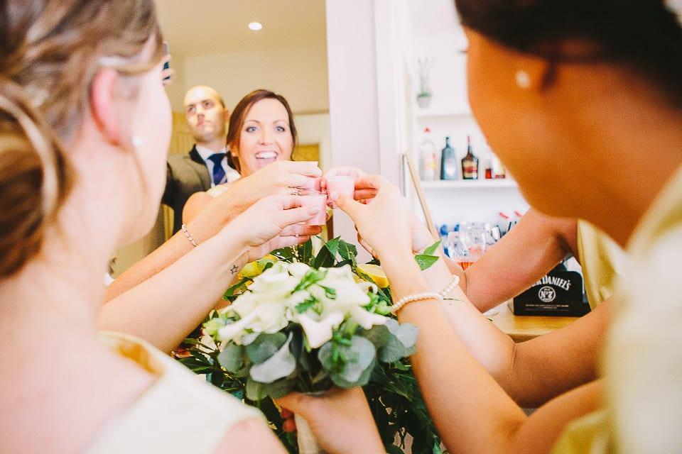 Bridesmaids all giving a toast at the bar at Sopley Mill