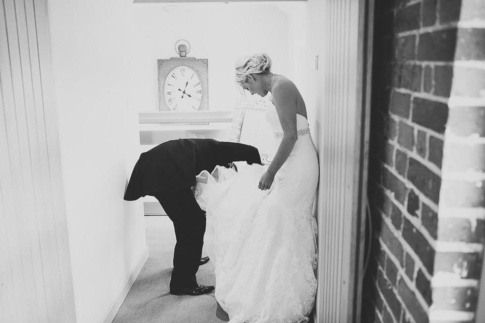 Groom helping bride sort out her dress before going into wedding breakfast at Sopley Mill