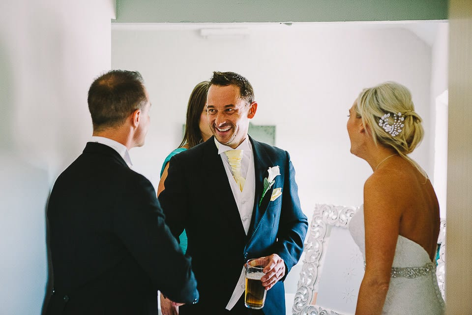Groom shaking hands with a friend in the receiving line at Sopley Mill