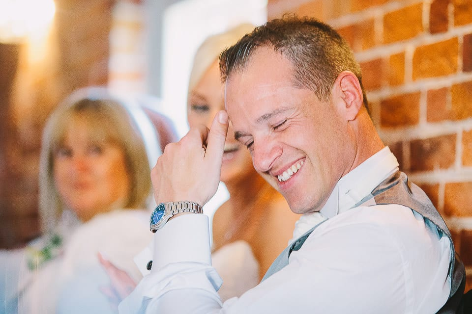 Bride and groom laughing during the speeches at Sopley Mill