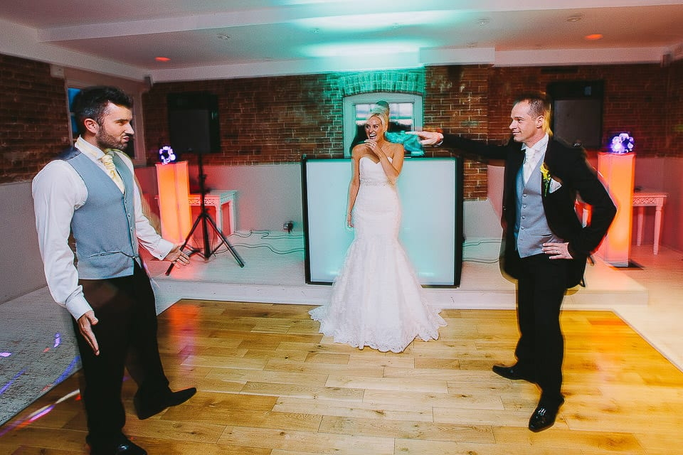 Groom surprising bride with a dance with all his groomsmen at Sopley Mill