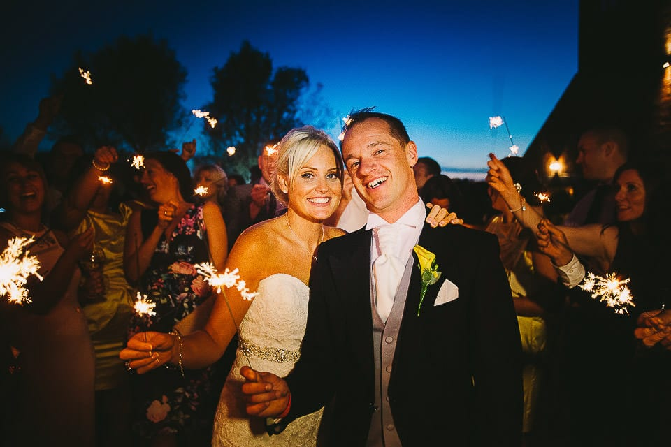 Bride and groom with sparklers at night at Sopley Mill