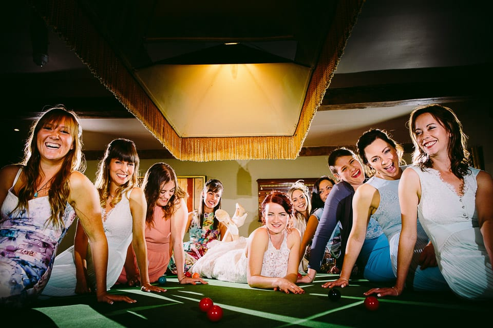 Bride on snooker table surrounded by her girls