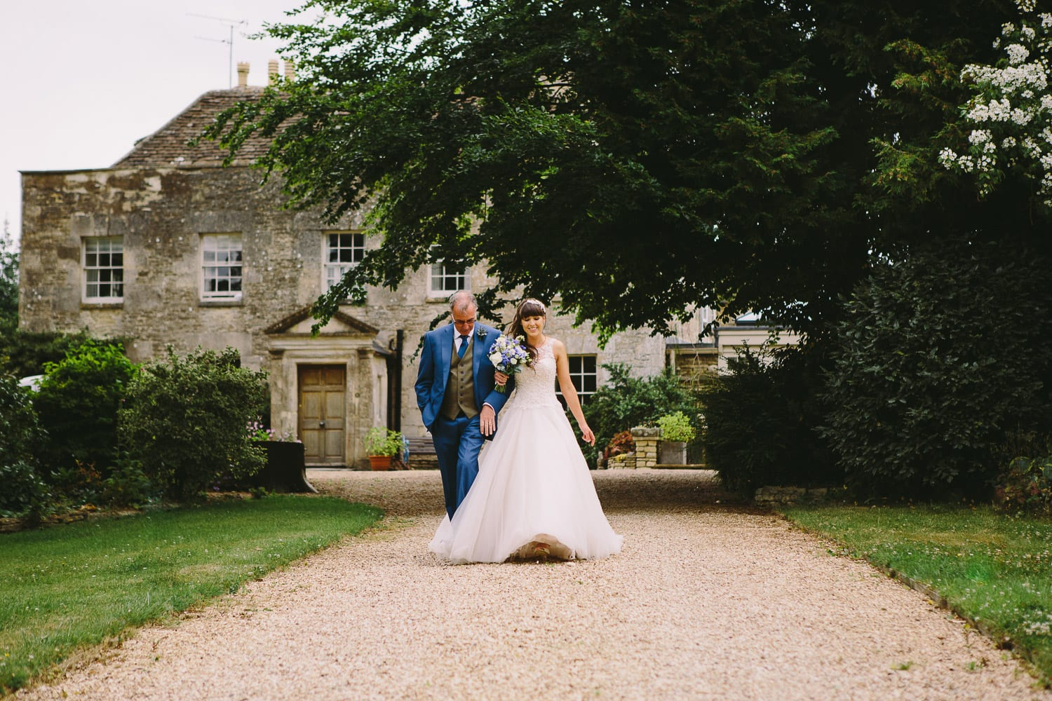 The bride and her father walk from the house to the outdoor wedding ceremony
