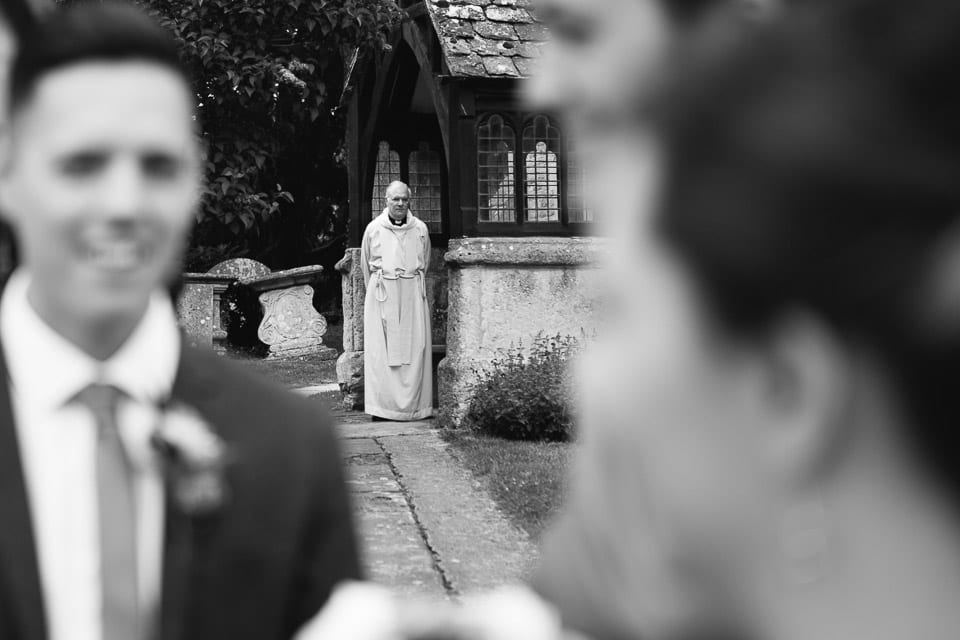 Black and white image of vicar waiting outside church