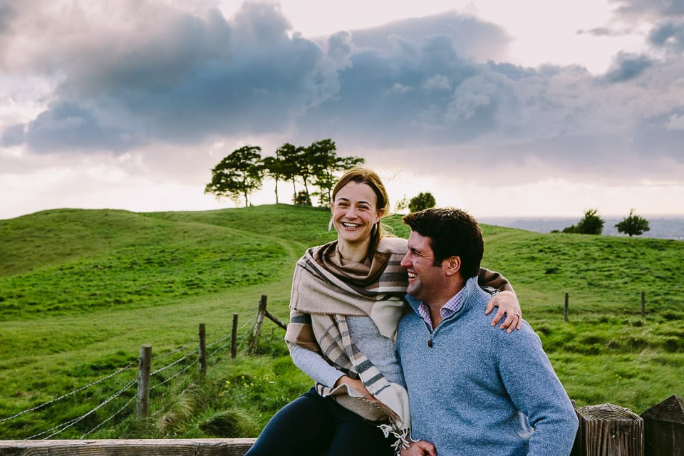 Engaged couple sitting on a fence at White Horse Cherhill