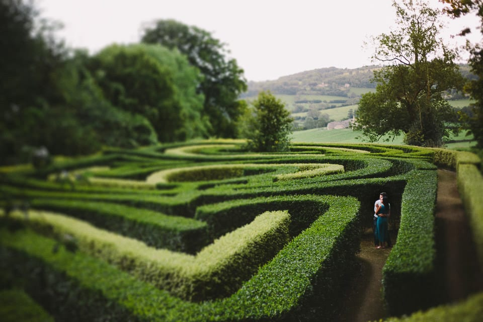 Engaged couple standing in a maze at Rococo Gardens