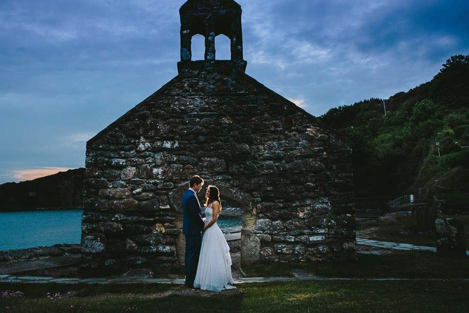 Bride and groom next to church ruin