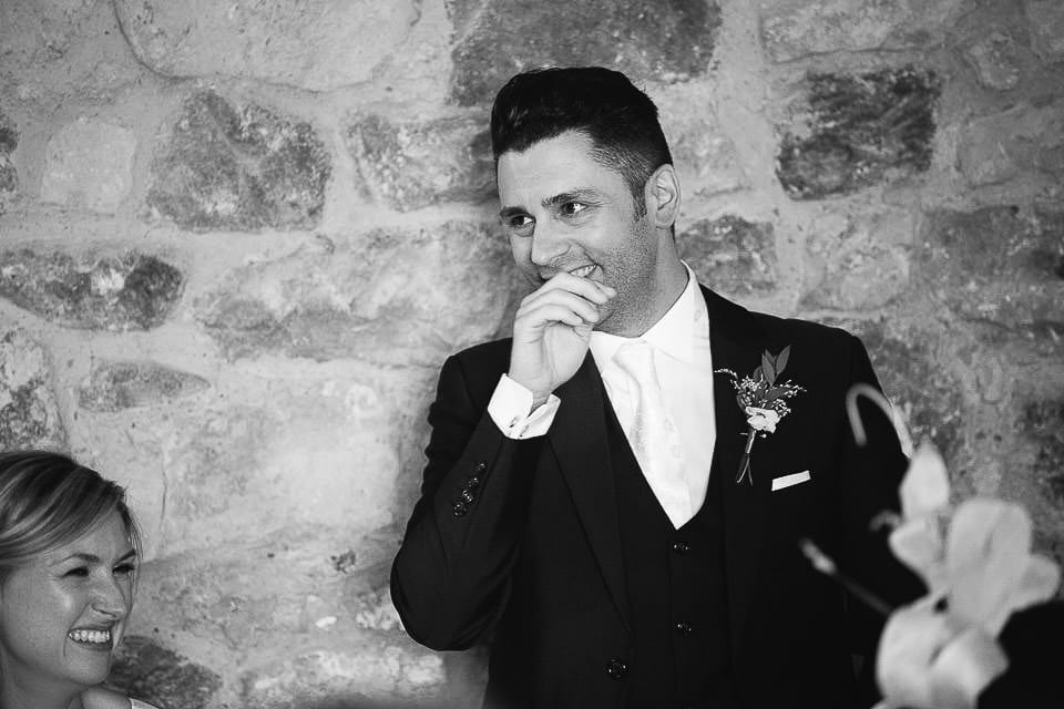 Black and white image of groom doing speech