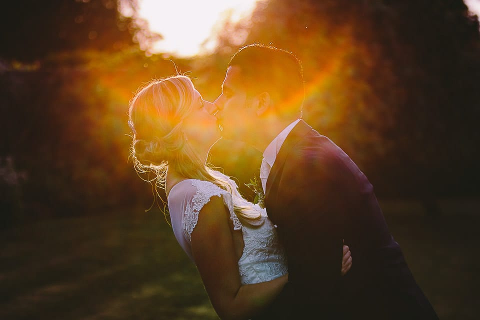Sunset image of bride and groom kissing
