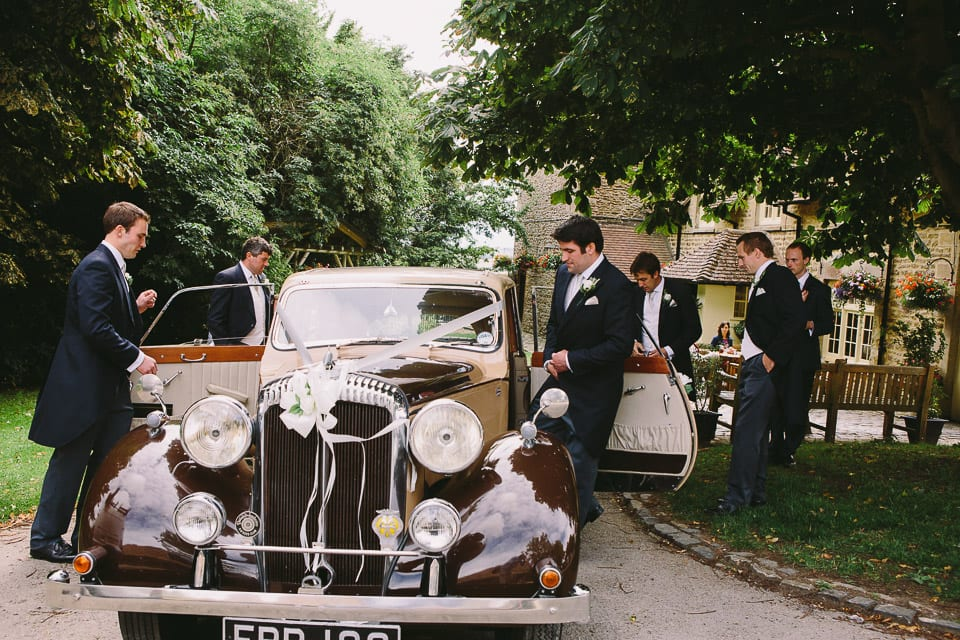 Groom getting into wedding car at pub