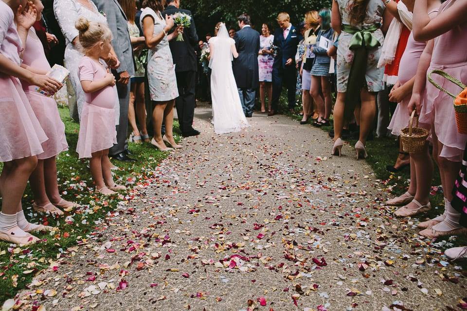 Confetti covered path with bride and groom from behind