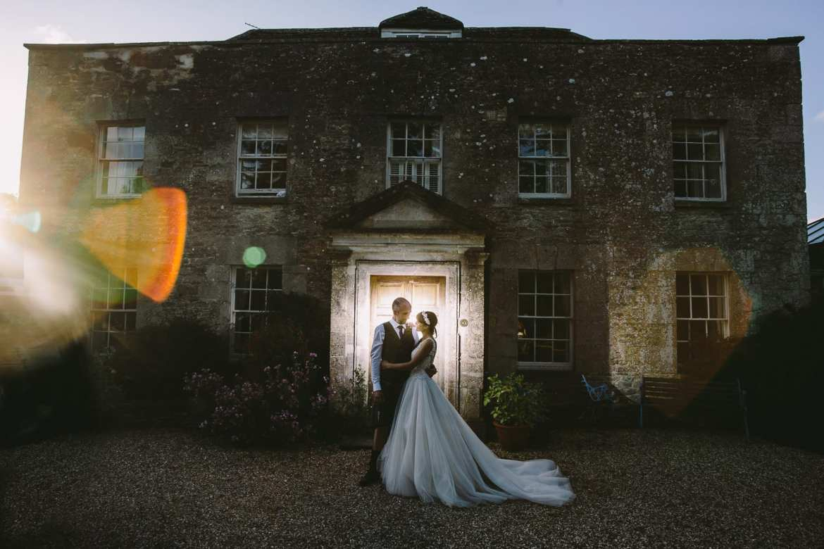 Backlit image of bride and groom outside main house