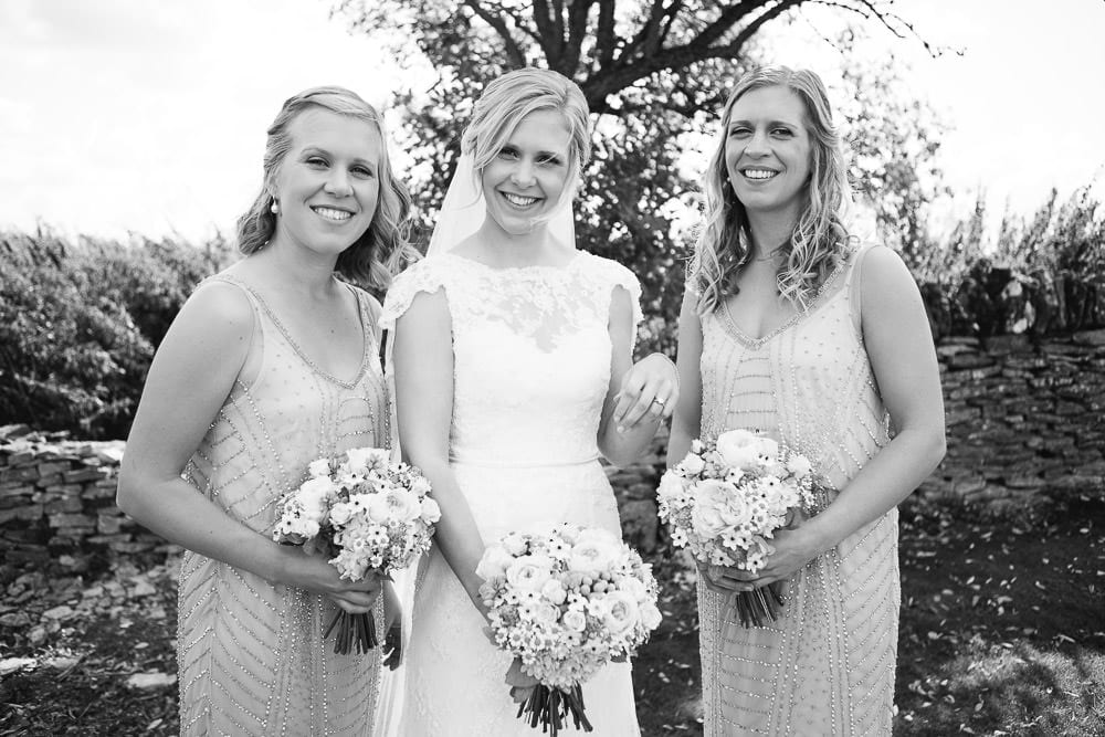 Black and white image of bride and bridesmaids in the gardens of Cripps Stone Barn