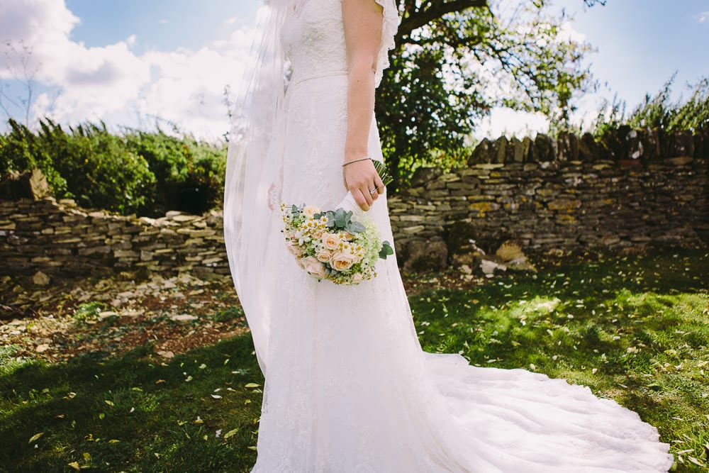 Bride holding her bouquet down by her side in the garden