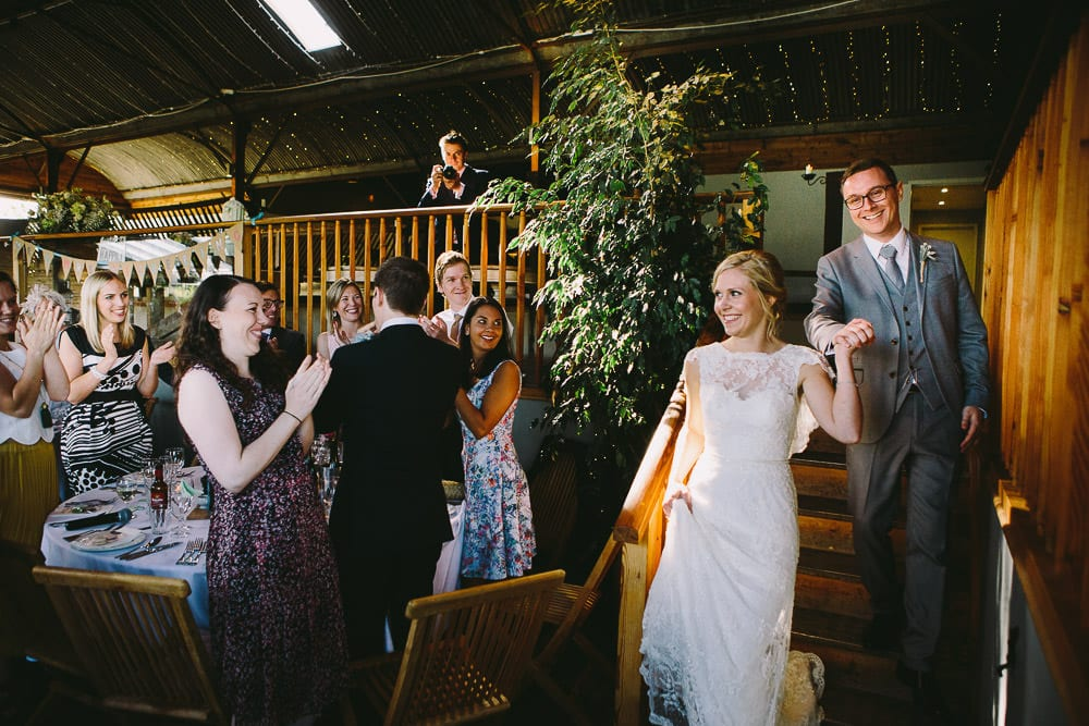 Bride and groom make their entrance for the wedding breakfast at Cripps Stone Barn