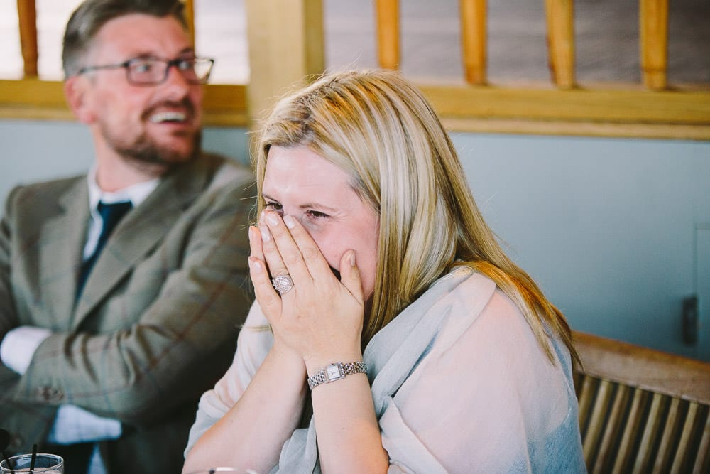Female guest laughing during the best mans speech at Cripps Stone Barn