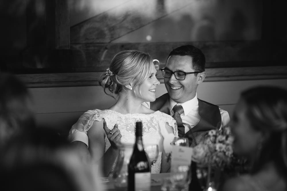 Black and white image of bride and groom enjoying the speeches at Cripps Stone Barn