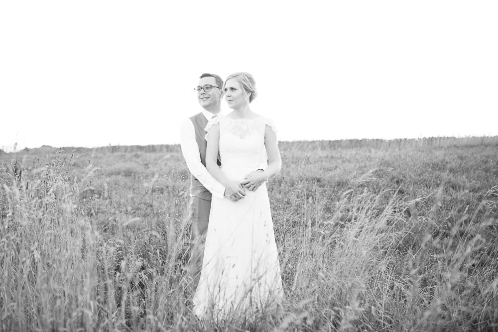 Black and white portrait of bride and groom in the field next to Cripps Stone Barn