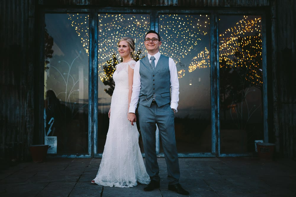 Portrait of bride and groom outside the main doors of the Dutch barn at Cripps Stone Barn