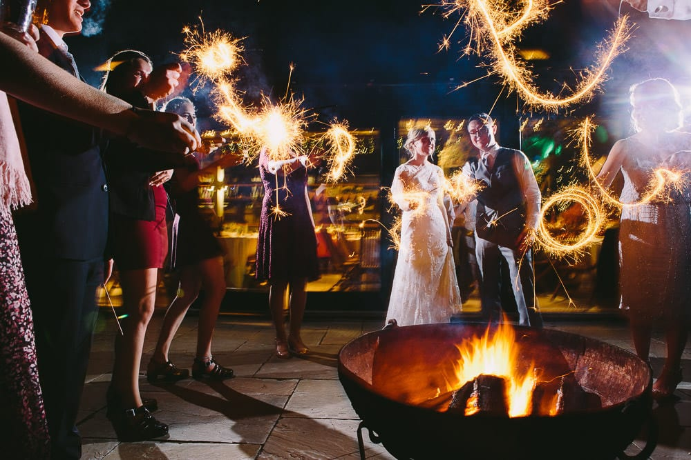 Bride and groom and their guests playing with sparklers by the fire pit at Cripps Stone Barn
