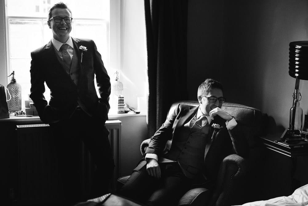 Best man and groomsman listening to groom practice his speech
