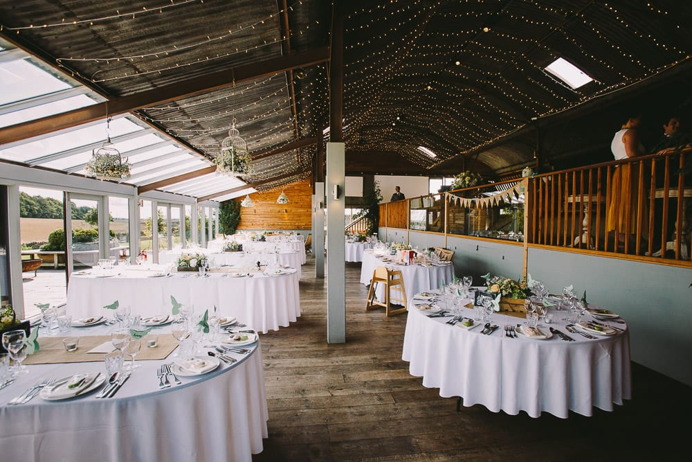 View of the Dutch barn set up for wedding breakfast at Cripps Stone Barn