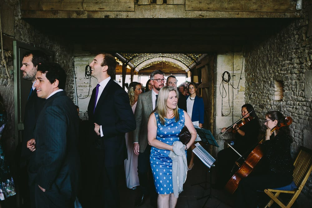 Guests making their way to their seats in the stone barn
