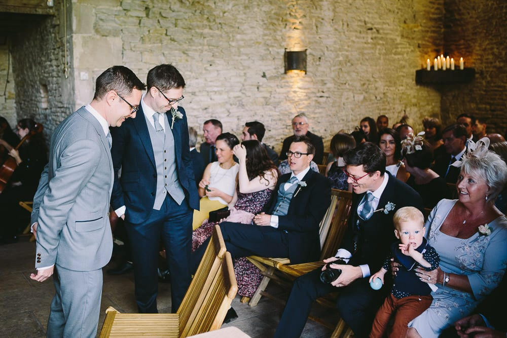 Groom chatting to guests in the stone barn ahead of the ceremony at Cripps Stone Barn