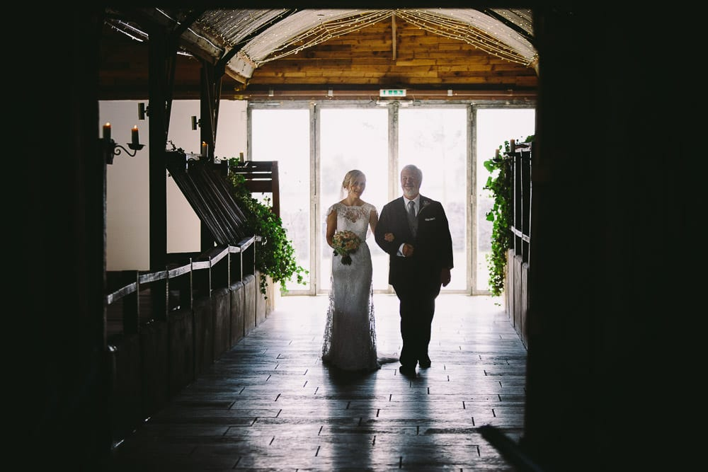 Bride and her father walking down through the Dutch barn at Cripps Stone Barn