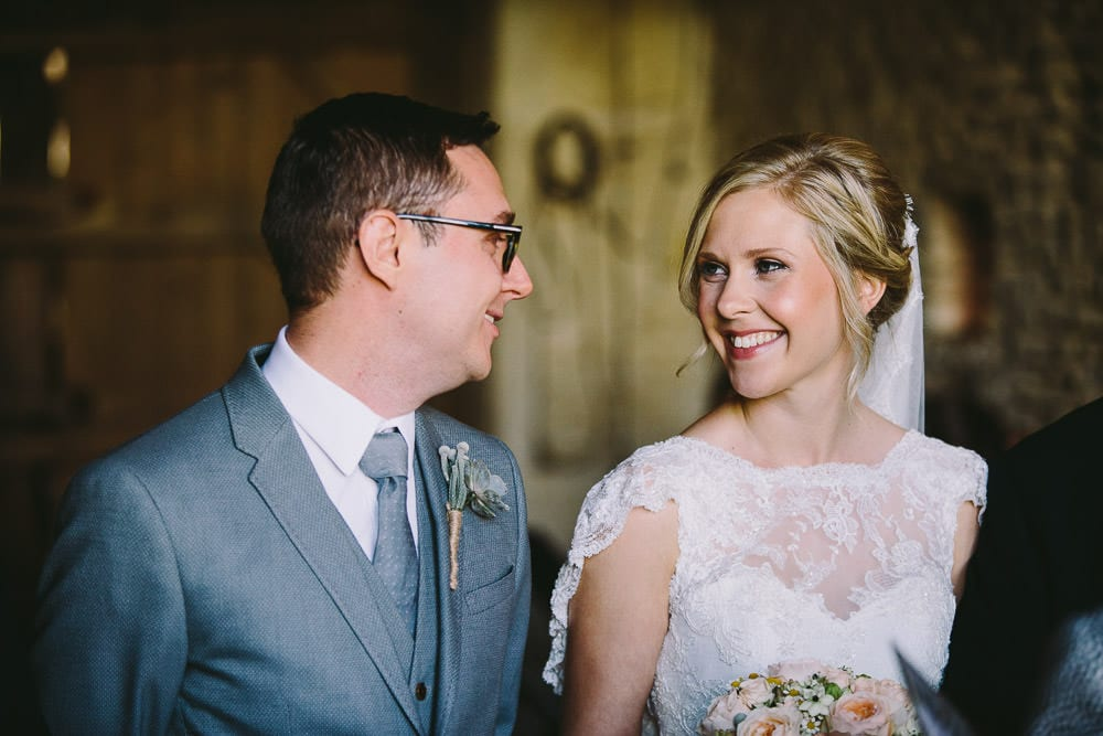 Bride and groom looking at each other during ceremony at Cripps Stone Barn