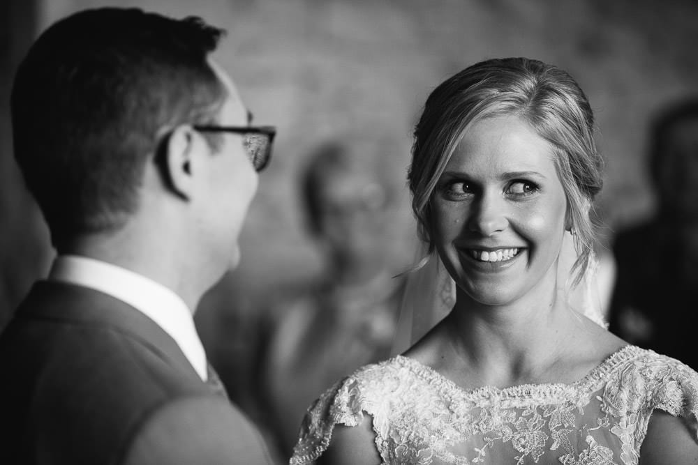 Black and white image of bride and groom during ceremony at Cripps Stone Barn