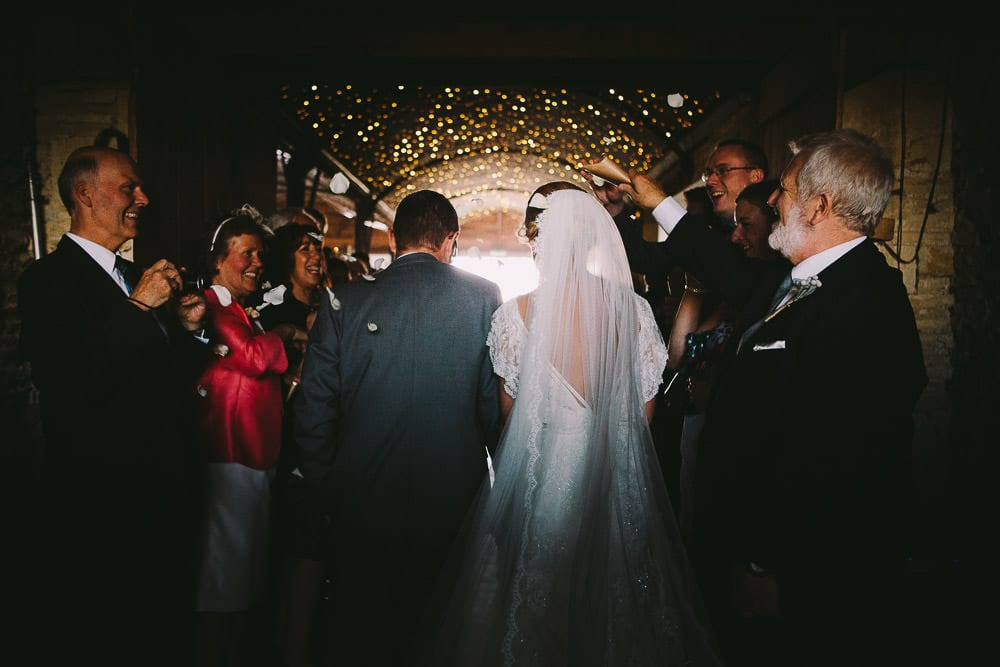 Bride and groom walking through confetti inside the Dutch barn at Cripps Stone Barn