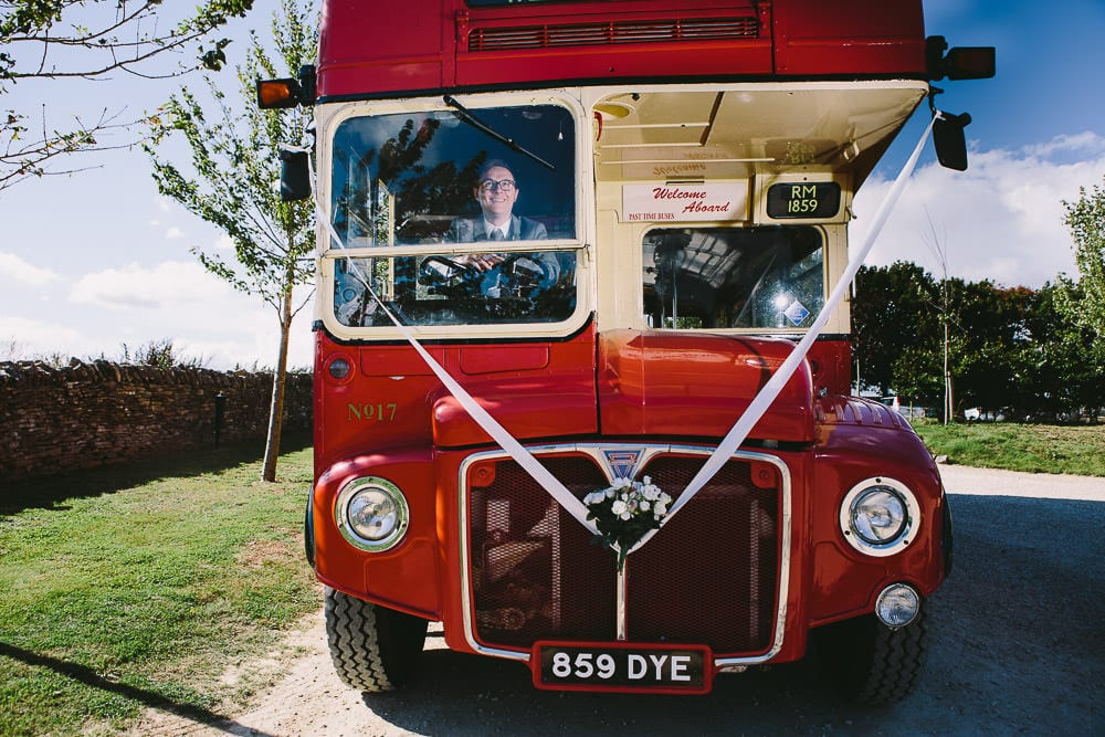 Groom at the wheel of the vintage routemaster bus outside Cripps Stone Barn