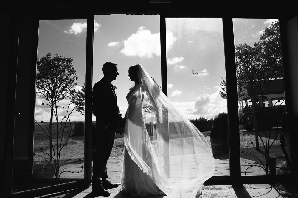 Black and white image of bride and groom standing by the doors of Cripps Stone Barn