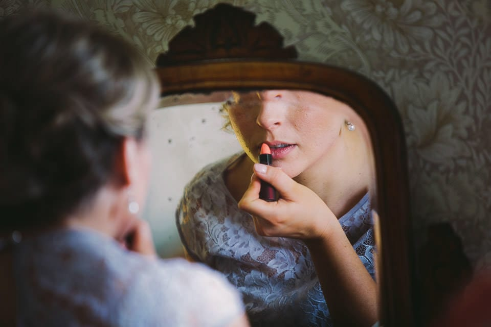 Bridesmaid putting her lipstick on in the mirror