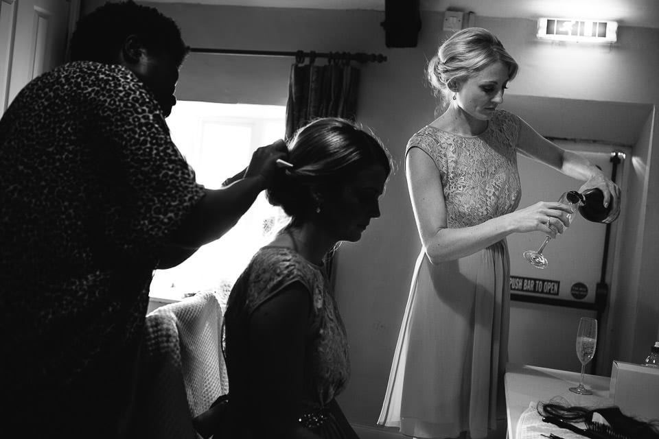Black and white image of bridesmaid having her hair done