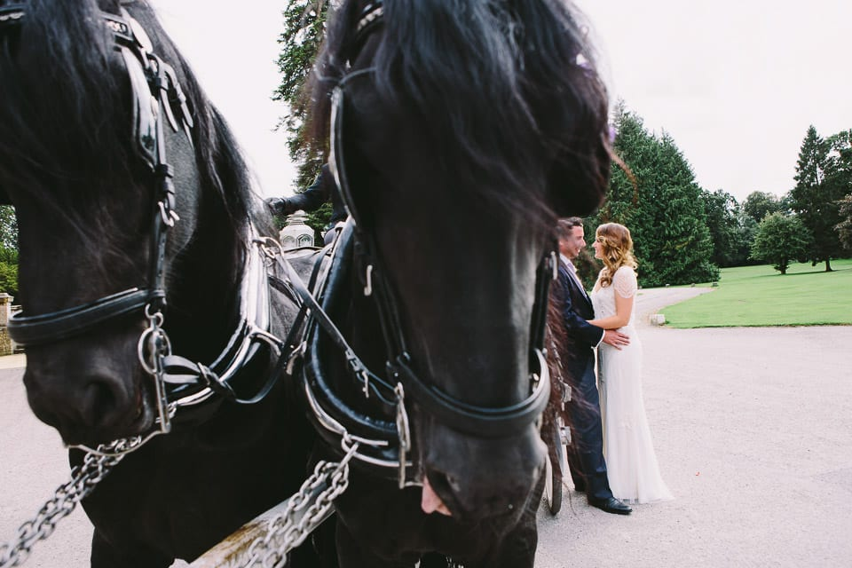 Bride and groom next to horse drawn carriage
