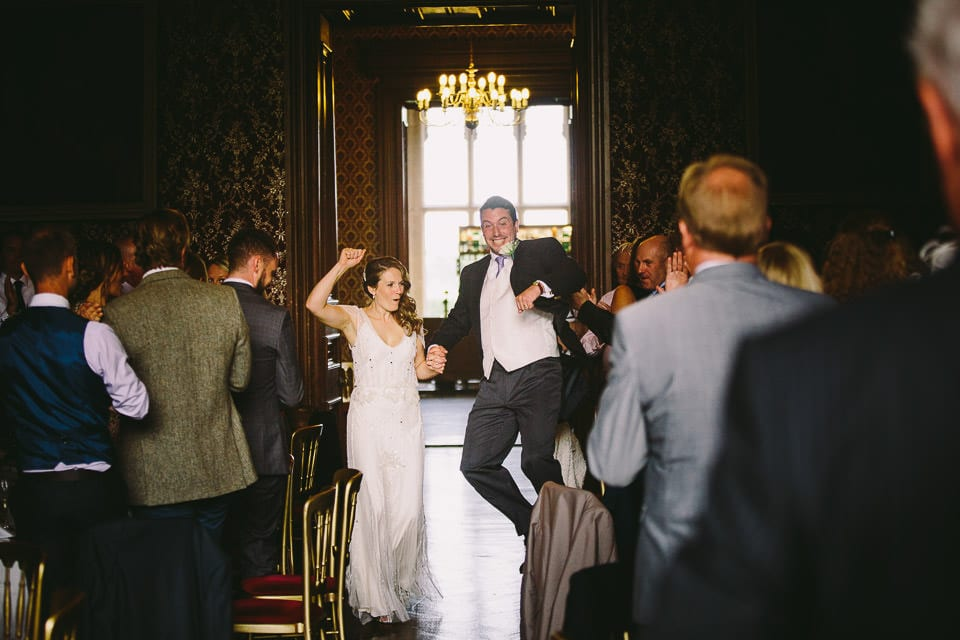 Groom leaping in the air while entering wedding breakfast