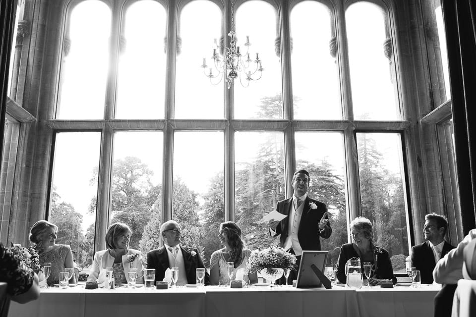Black and white image of top table and groom doing speech