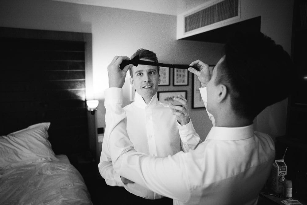 Groom holding the other grooms tie in the hotel room