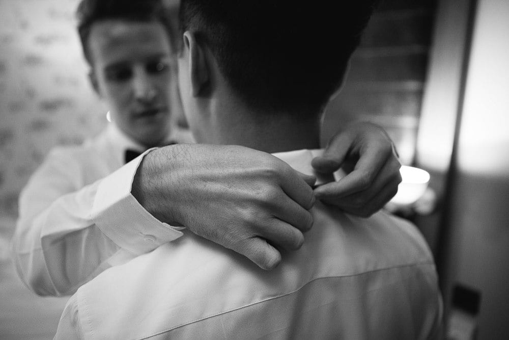 Black and white close up of groom tying his grooms bow tie at The Hoxton London